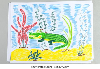 Kid doodle of cute crocodile underwater on sand bottom with seaweeds - bright felt-tip pen scribble child drawing of green water animal reptile and plant.
