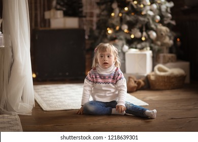 kid with down syndrome with a gift near the christmas tree the concept of christmas