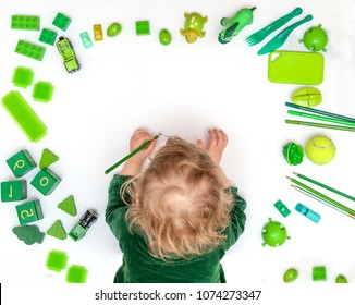 Kid drawing on floor on paper. Preschool child plays on floor with educational toys - blocks, train, railroad, plane. Toys for preschool and kindergarten. Children at home or daycare. Top view