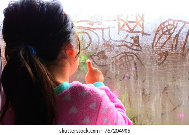 kid drawing on raining window
