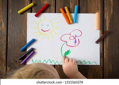 kid drawing on wooden table