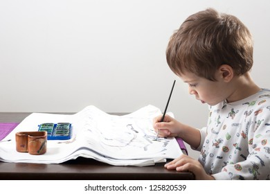 Kid drawing with water colors on table