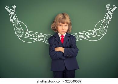 Kid with drawn robot hands against blackboard. Schoolchild in class