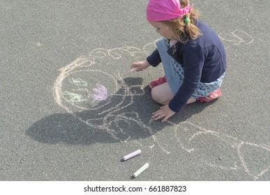 the kid draws mom on asphalt on a summer day.