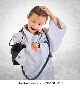 Kid dressed like doctor doing surprise gesture