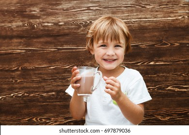 the kid drinking cocoa at home against the background of a wooden wall