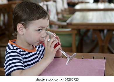 Kid drinking juice at table in cafe