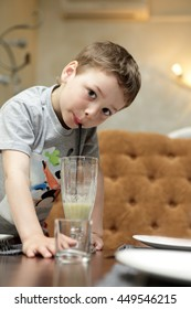 Kid is drinking smoothie in a cafe