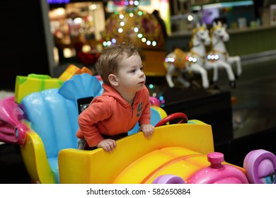 Kid driving toy car in amusement park