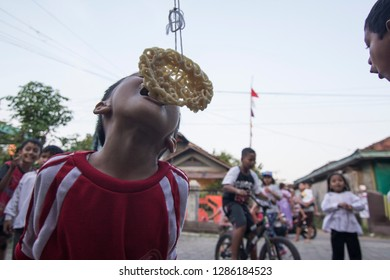 Kid eating hanging cracker in Eating cracker competition, Lomba makan krupuk to celebrate Indonesia independence day, Kudus, Jawa Tegah, Indonesia, 17 August 2016