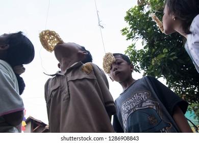 Kid eating hanging cracker in Eating cracker competition, Lomba makan krupuk to celebrate Indonesia independence day, Kudus, Jawa Tengah, Indonesia, 17 August 2017