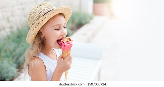 Kid is eating ice cream. Happy Little girl is enjoying italian gelato in town. Cute child in straw hat is tasting delicious street food in summer travel outdoors. Light background, free space for text