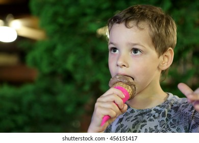 Kid eating ice cream in park at night