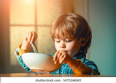 Kid eating. Little boy having breakfast in the kitchen. Cute child eating breakfast at home. Baby eating