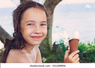 Kid eating soft serve ice cream on beach. Cute Little Girl after swimming enjoying summer holidays vacation outdoor.