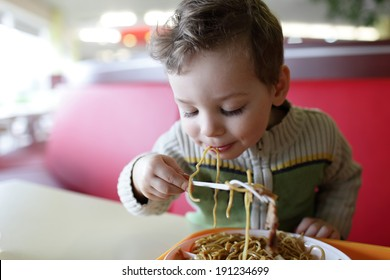 The kid eating spaghetti in the restaurant