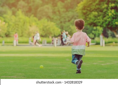 Kid enjoy playing with little ball on green field