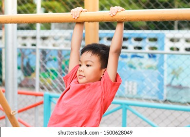 Kid exercise for health and sport concept. Happy Asian child boy playing and hanging from a steel bar at the playground. 5 years old.