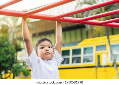 Kid exercise for health and sport concept. Happy Asian student child boy playing and hanging from a steel bar at the playground. 6-7 years old.