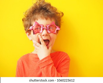 Kid in eyeglasses in shape of star makes face. Funny big star. Yellow background.