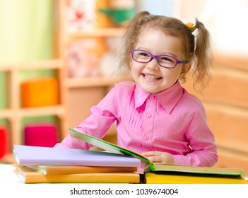 Kid in eyeglasses or spectacles reading books in her room