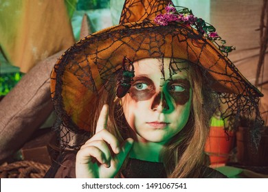 Kid eyes with skull make up. Little Witch. Funny child girl with skeleton costume holding skull and eating candies. Happy funny little girl with Halloween pumpkin make funny face