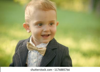 Kid fashion, beauty, style. Little boy with bowtie on natural landscape, fashion. Child smile with bow tie on summer day, vacation. Happy childhood, youth. Vacation, activity, lifestyle