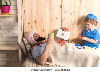 Kid and father playing hospital. Patient with flu lying in bed under woolen blanket. Doctor visiting sick bearded man at home, educational game concept.