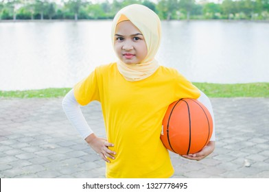 Kid female in hijab play basketball in park