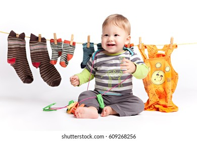The kid finished hanging washed laundry and drying socks and laughs holding clothespins