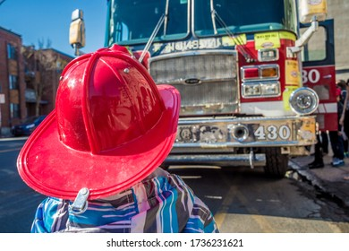 Kid with a fire fighter helmet in front of a fire truck in Montreal, Canada