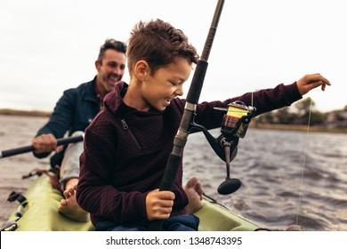 Kid fishing in lake with his father. Kid releasing the thread tied to the fishing rod in the lake to catch fish.