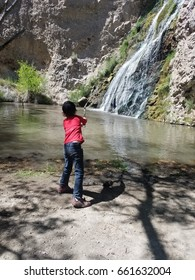 Kid fishing near waterfall