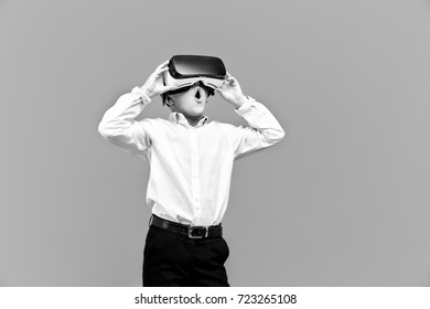 Kid in formal outfit wearing VR glasses putting hands on it in excitement isolated on grey background.