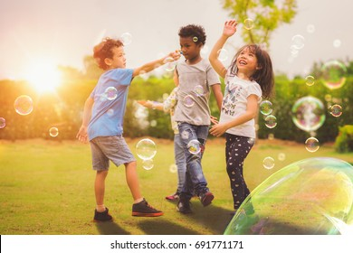 Kid and friends in international preschool play a bubble in playground with sunset background, kid, child, school, play and summer background
