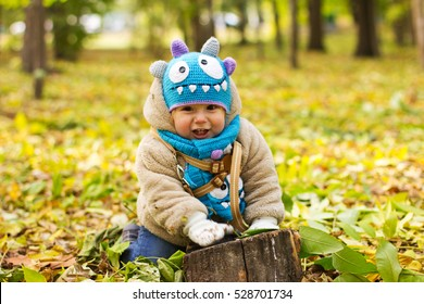 Kid in a funny hat. The boy walks in the fresh air. The kid is playing in the yellow leaves.