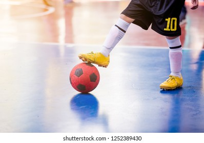 Kid futsal player  trap and control the ball for shoot to goal. Soccer players fighting each other by kicking the ball. Indoor soccer sports hall. Football futsal player, ball