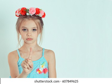kid gesturing a no sign. portrait unhappy, serious child girl raising finger up saying oh no, you do not have to do that isolated white green background. Negative emotions, facial expressions feelings
