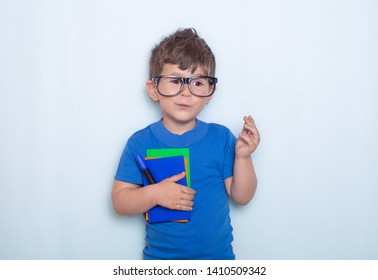 Kid gets ready for school. Schoolboy holding school supplies: pen, notebooks. Back to school concept. Space for text, isolated.