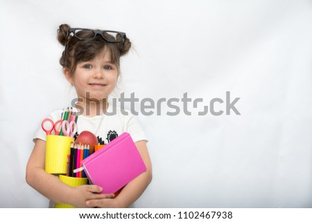 3f9243bfee47 Kid gets ready for school. Schoolgirl holding many school supplies  pens