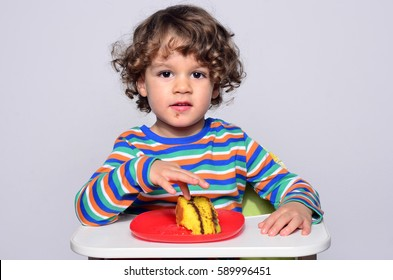 Kid getting messy while eating a chocolate cake. Beautiful curly hair boy eating sweets. Toddler in high chair being hungry.