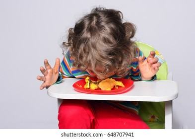 Kid getting messy while eating a chocolate cake. Beautiful curly hair boy eating sweets. Toddler in high chair being hungry stuffing his mouth with cake