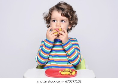 Kid getting messy while eating a chocolate cake. Beautiful curly hair boy eating sweets. Toddler in high chair being hungry stuffing his mouth with cake.