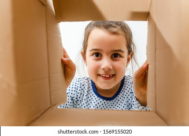 kid girl age 7 year unpacking and opening carton box, and looking inside with surprise