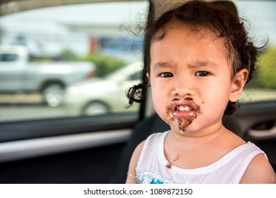 Kid girl asia eating ice cream. kid with a dirty face from eating a ice cream chocolate dessert