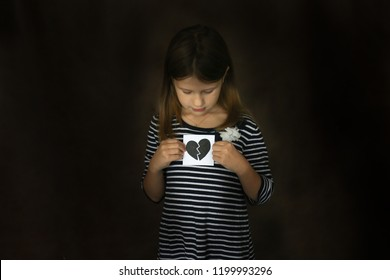 Kid girl with a broken heart on paper, the concept of children's emotions and tragedy