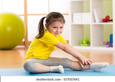 Kid girl doing fitness exercises at home in her room