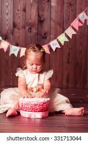 Kid girl eating birthday cake sitting on wooden floor in room. Wearing princess dress. Childhood. First birthday.
