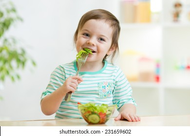 kid girl eating healthy vegetables at kitchen