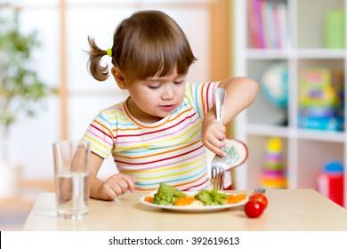 kid girl eating healthy vegetables in kindergarten or nursery
